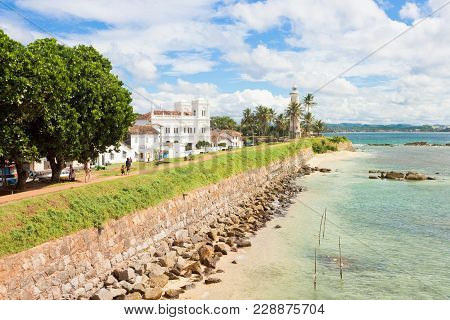 Galle, Sri Lanka, Asia - December 2015 - People Walking On The Historical Town Wall Of Galle In Fron