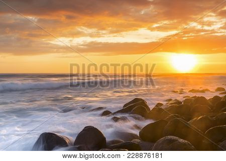 Colourful Red Sunrise Lighting Up The Sky With Ocean Tide Over Rocks
