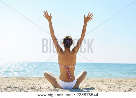 Beautiful Sexual Young Woman In White Bikini Sits On The Beach Against The Sea And Sky At Sunny Day