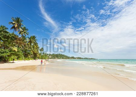 Mirissa Beach, Sri Lanka, Asia - December 2015 - Tourists Walking On The Sand While Enjoying The Vie