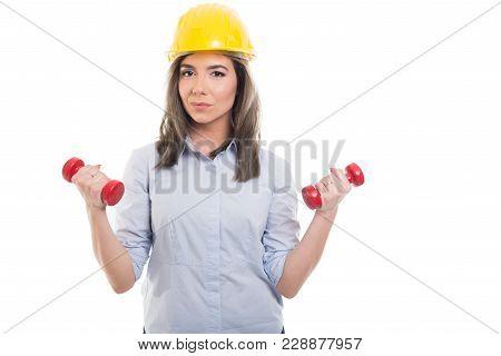 Female Constructor Wearing Hardhat Holding Dumbbells.