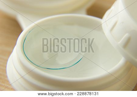 Contact Lenses For The Eyes Close-up And A White Container With A Solution On A Wooden Table