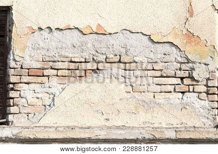 Old Damaged Brick Wall With Bad Foundation Base And Peeled Plaster Almost Collapsed
