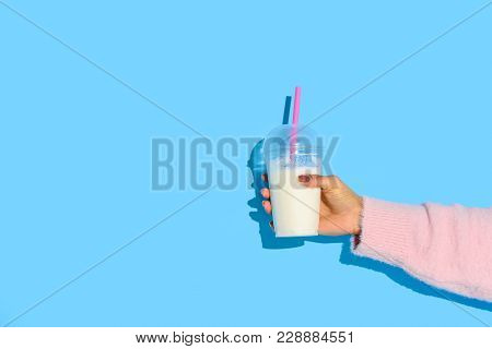 Partial View Of African American Woman Holding Glass Of Milk With Straw Against Blue Background