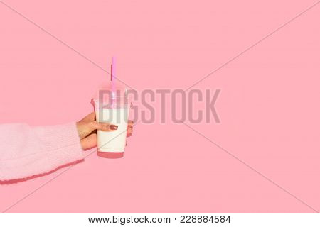 Partial View Of African American Woman Holding Glass Of Milk With Straw Against Pink Wall