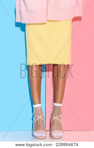 Partial View Of African American Woman In Stylish Clothing Against Pink And Blue Wall