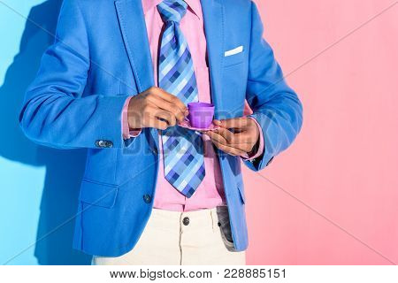 Partial View Of African American Man With Toy Teacup In Hands With Pink And Blue Background