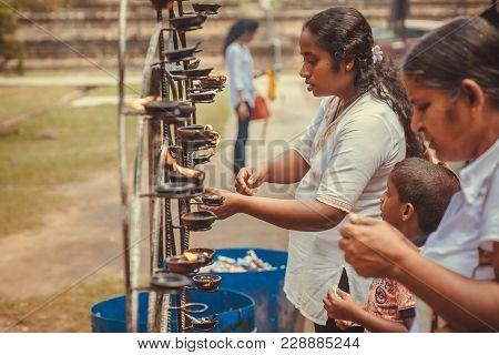 Kandy, Sri Lanka - Jan 5, 2018: Families Of Praying People Lighting The Oil Lamps Near The Buddhist