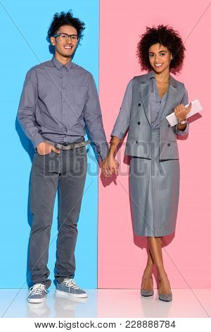Young African Amercian Girl Holding Tablet And Hand Of Stylish Guy On Pink And Blue Background