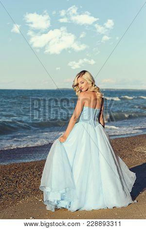Woman With Blue Evening Dress On The Beach