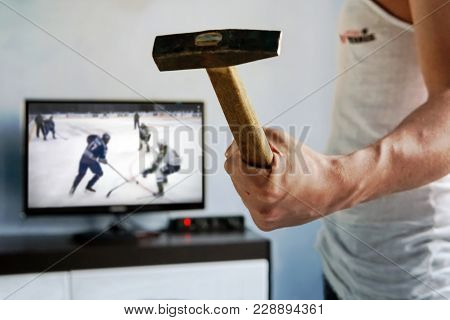 A disgruntled fan is disappointed by the loss of their favorite team. man wants to break the TV. The guy swung a hammer at the screen. Emotional fans watching the  hockey poster