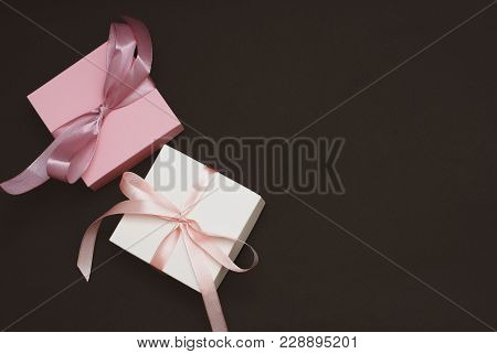 White And Pink Gift Box With A Pink And White Ribbon Bow On A Pink Wooden Background. Flat Lay, Top