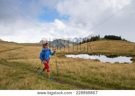 Lonely Girl Practicing Nordic Walking With Hiking Sticks In The Mountains