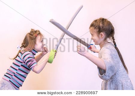 Two Girls With Toy Swords Play Knights. Children's Emotions.