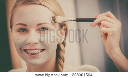 Happy Young Woman Applying Mud Mask On Face