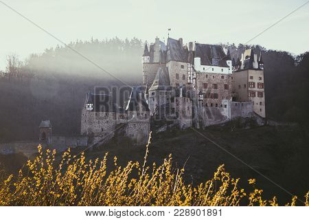 Beautiful View Of Famous Eltz Castle In Scenic Golden Morning Light At Sunrise In Fall With Retro Vi