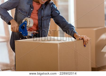 Cropped View Of African American Woman Packing Cardboard Box With Scotch Tape