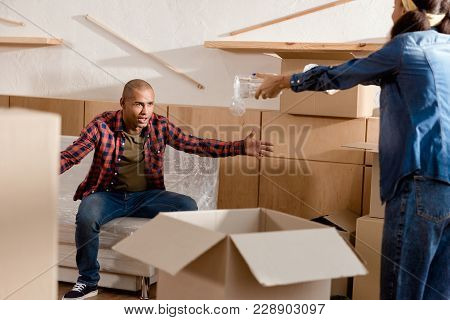 African American Couple Packing And Quarreling In New Apartment With Cardboard Boxes