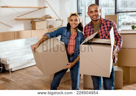 Happy African American Couple Holding Cardboard Boxes And Moving To New Home