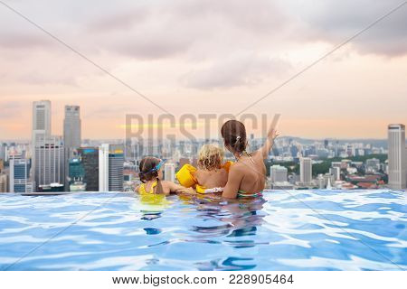 Family Swimming In Roof Top Outdoor Pool On Family Vacation In Singapore. City Skyline From Infinity