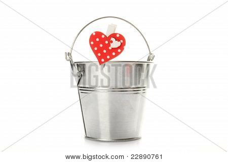 Metal bucket isolated on a white background. On the bucket wooden clothespin with a red heart poster