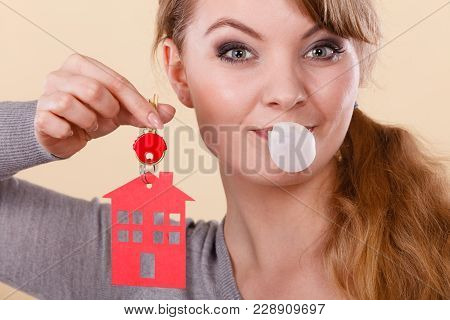 Young Happy Woman Doing Bubble With Chewing Gum While Holding New House Key With Red Home Shape. Rea