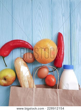 Paper Bag With Different Useful Food On Blue Wooden