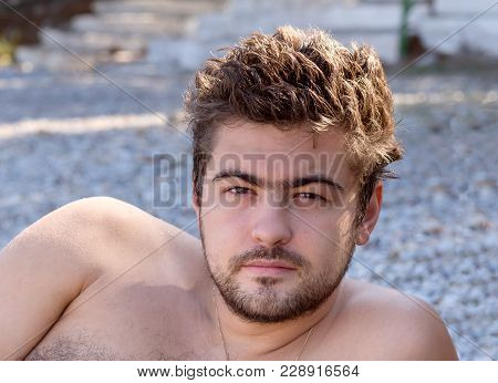 Portrait Of A Young, Cute Male With Disheveled Hair Resting On The Beach In The Summer Time.