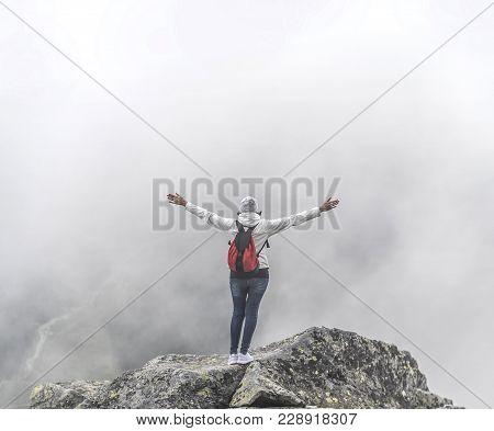 Tourist On The Top Of A Mountain Peak. The Traveler Celebrates The Ascent To The Mountain Peak. Free