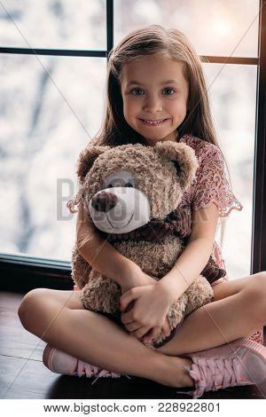 Happy Little Child Sitting On Windowsill With Teddy Bear