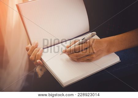 Female Casual Creative Designer Worker Is Writing Note On Notebook