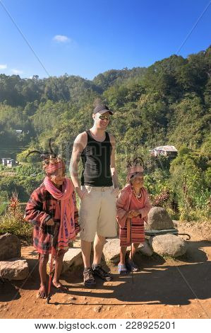 Banaue, Philippines - February 6th, 2013: Old Ifugao Couple With Big Tourist Compare Their Sizes In
