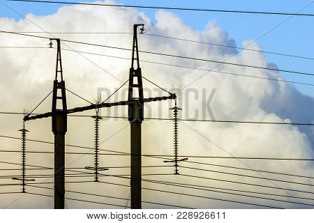 Electricity Transmission Power Lines Against White Clouds. High Voltage Towers