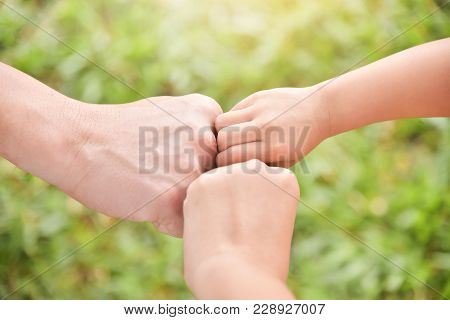 Close Up Man, Woman And Kid Fist Or Hands Join Together On Grass Background At Park Outdoor. Family.