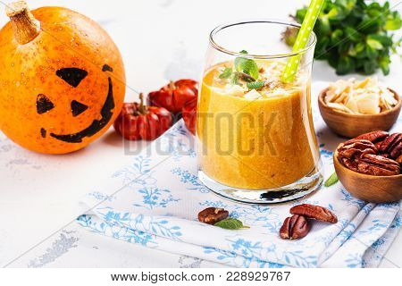 Pumpkin Smoothie With Coconut Chips, Pecan Nuts, Cinnamon And Mint. Halloween Party Treat On Spooky
