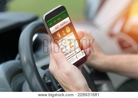 Betting on sports, holding smart phone with working online betting mobile application while driving a car poster