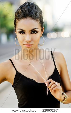 Beautiful young woman hair pulled back stylishly posing outdoors in urban city setting.