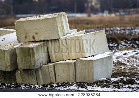 Stack Of Concrete Blocks For Foundation On Construction Site. Ferroconcrete Reinforced With Metal Bl