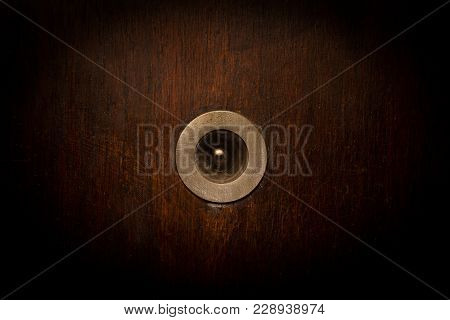 Front View Closeup Of Vintage Metallic View Finder On Blown Scratched Wooden Door Texture