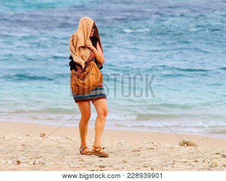 A chilly woman walking and shaking on the beach. End of summer with bad weather.