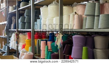 Spools With Different Color Thread On Shelves At Knitting Shop View