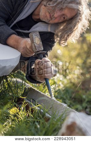 Sculptor Sculpting With Chisel And Hammer In Marble Stone Outdoors.