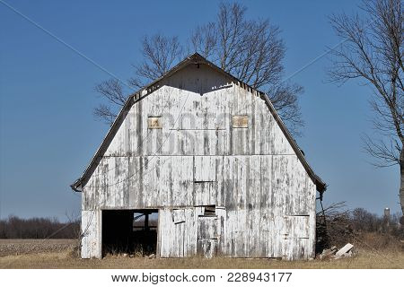 An Abandoned White Barn On A Farmstead In Rural America.