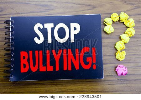 Handwritten text showing Stop Bullying. Business concept writing for Prevention Problem Bully Written on notepad paper, wooden background in office view with question mark on the end. poster