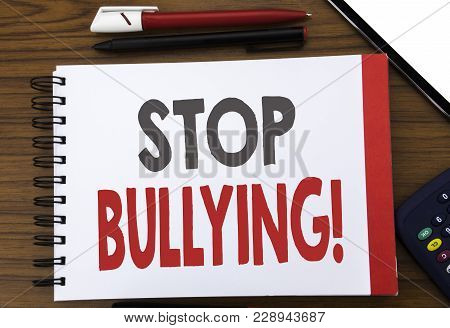 Handwritten text showing Stop Bullying. Business concept writing for Prevention Problem Bully Written on notepad paper, wooden background in office view with pencil marker calculator poster