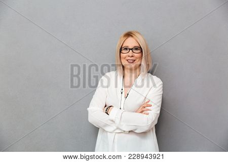 Pleased middle-aged blonde woman in shirt and eyeglasses posing with crossed arms and looking at the camera over grey background