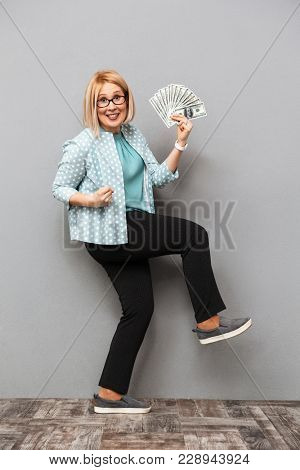 Full length image of Cheerful middle-aged blonde woman in blouse and eyeglasses holding money while rejoices and looking at the camera over grey background