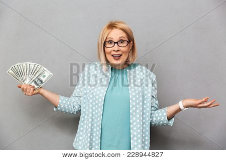 Confused happy middle-aged blonde woman in blouse and eyeglasses shrugs her shoulders while looking at the camera over grey background