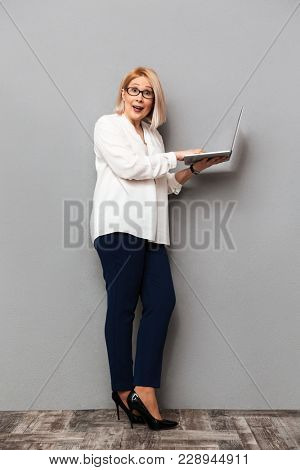 Full length image of Surprised middle-aged blonde woman in elegant clothes and eyeglasses posing sideways while holding laptop computer and looking at the camera over grey background