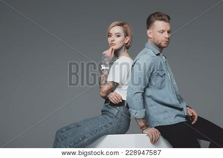 Stylish Young Tattooed Couple Sitting Back To Back And Looking At Camera Isolated On Grey